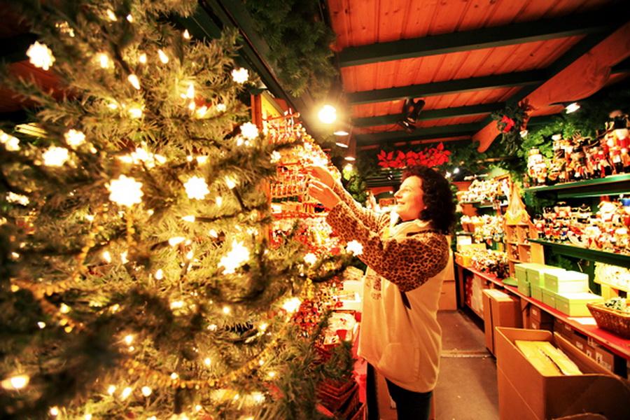 Eine Mitarbeiterin dekoriert am Freitag (20.11.2009) in der Altstadt in Lübeck eine Weihnachtshütte. Vom 23. November bis zum 30. Dezember 2009 bieten über 200 Schausteller in ihren Buden vom Glühwein bis zum Weihnachtsschmuck alles, was Besucher in Weihnachtsstimmung versetzen kann. Der Besuch des Lübecker Weihnachtsmarkts, der bereits 1648 erstmals urkundlich erwähnt wurde, gehört zu den vorweihnachtlichen Höhepunkten in der Hansestadt. Foto: Bodo Marks dpa/lno +++(c) dpa - Report+++
